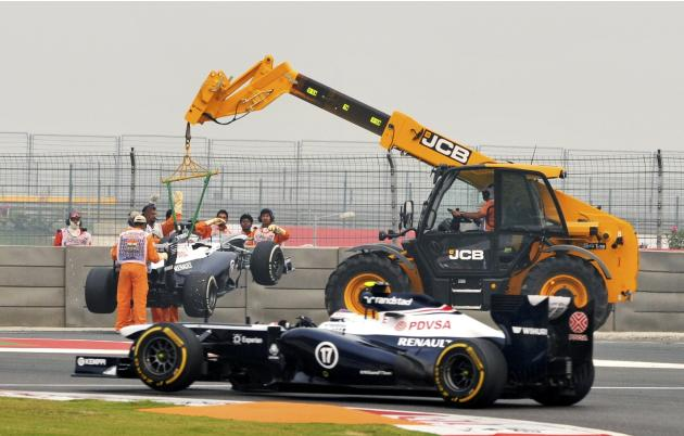 Williams Formula One driver Bottas drives past as the car of Williams Formula One driver Maldonado is lifted during the second practice session of the Indian F1 Grand Prix at the Buddh International C