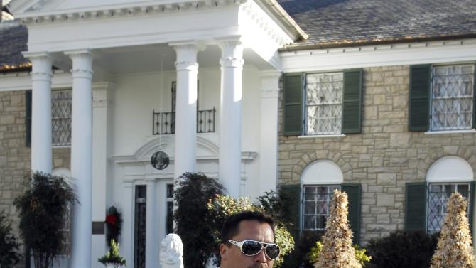 FILE - In this Jan. 7, 2011 file photo Chilean miner Edison Pena strikes an Elvis Presley pose outside the Graceland mansion in Memphis, Tenn. One of the myths surrounding the 33 miners who survived 69 days, 700 feet deep, and whose unprecedented and dramatic rescue was beamed to millions around the world, is that they are millionaires and do not need work. A year after the tragedy, nearly half are unemployed, one lives the fame that began to take shape at the bottom of the mine, many have chosen to give motivational talks to make a living and only four have returned to work in a cave. (AP Photo/Mark Humphrey, File)