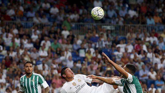 Real Madrid's Rodriguez scores his second goal between Real Betis' Vargas and Van der Vaart during their Spanish first division soccer match at Santiago Bernabeu stadium in Madrid, Spain