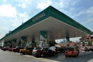Taxis queue up at a Petronas petrol station in Kuala Lumpur. Malaysian state energy firm Petronas has agreed to buy Canada's Progress Energy Resources for $5.3 billion to secure stable supplies of liquefied natural gas (LNG) from North America, it said