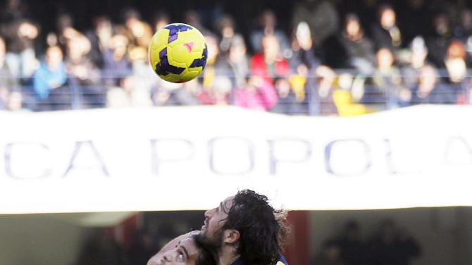 Juventus' Martin Caceres, left, of Uruguay, and Verona's Luca Toni fight for the ball during a Serie A soccer match at Bentegodi stadium in Verona, Italy, Sunday, Feb. 9, 2014