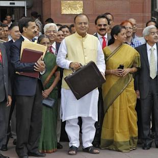 India's FM Jaitley poses as he leaves his office to present the federal budget for the 2014/15 fiscal year in New Delhi