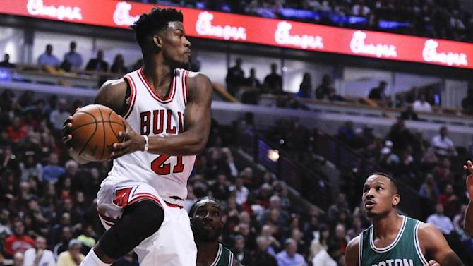 Chicago Bulls' Jimmy Butler (21) passes past Boston Celtics' Jae Crowder (99) and Avery Bradley (0) during the first quarter of an NBA basketball game Thursday, Oct. 27, 2016, in Chicago. (AP Photo/Matt Marton)