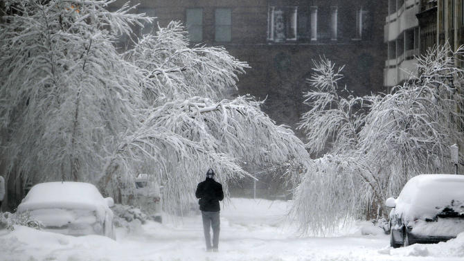 A pedestrian passes snow covers cars and trees Tuesday, Feb. 26, 2013 in Kansas City, Mo. The second major snowstorm in a week battered the nation's midsection Tuesday, dropping a half-foot or more of heavy, wet snow across Missouri and Kansas and cutting power to thousands.  (AP Photo/The Kansas City Star, Keith Myers)