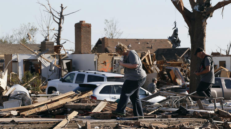 A couple tries to find valuables in their tornado-destroyed home in Moore
