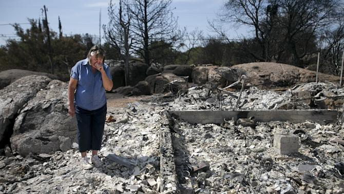 Yarnell Hill Fire Glen Ilah - Judy Aldridge, a resident of Glen Ilah, Arizona for 32- years, looks on in the debris of what was her home on Wednesday, July 10, 2013. Judy and her husband, Jack Aldridge are in the early stages of the clean up process after the Yarnell Hill Fire completely destroyed their home on June 30. (AP Photo/The Arizona Republic, David Wallace)