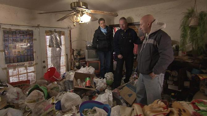 """Dr. Zasio Kieth and Dan stand on top of trash in the living room in the season premiere of """"Hoarders."""""""