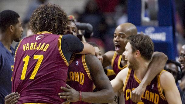 In this March 26, 2014 file photo, Cleveland Cavaliers guard Dion Waiters, second from left, is hugged by teammate Anderson Varejao (17) after sinking a two-point basket to defeat the Detroit Pistons in an NBA basketball game in Auburn Hills, Mich. With seven games left, and a favorable schedule the rest of the way, the Cavaliers are in the mix to make the playoffs for the first time since 2010, when LeBron James was in his final days wearing wine and gold