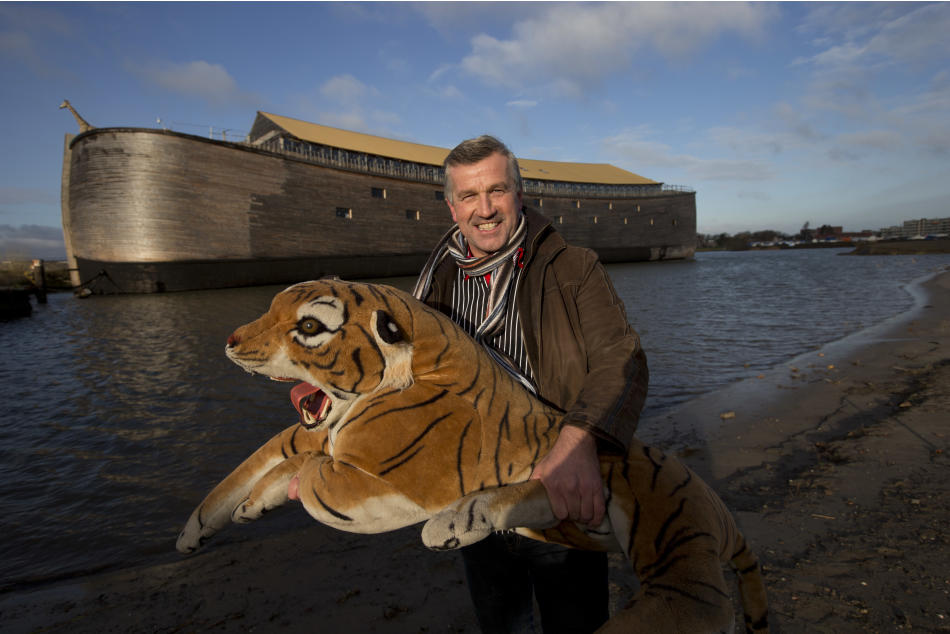 Johan Huibers poses with a stuffed tiger in front of the full scale replica of Noah's Ark after being asked by a photographer to go outside with the animal in Dordrecht, Netherlands, Monday Dec. 10, 2