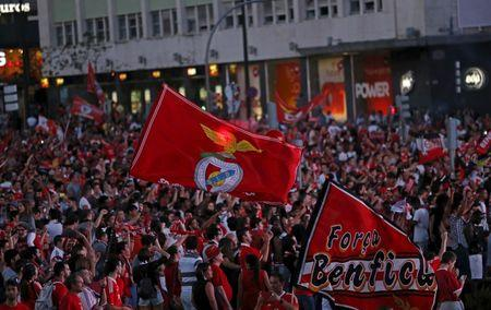 Benfica supporters hold the team flag at Marques Pombal Square after beating Guimaraes and winning the Portuguese Premier League title, in Lisbon