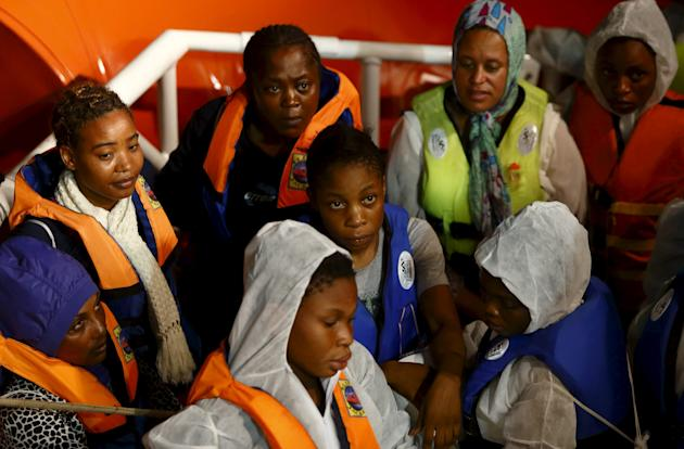 Rescued migrants stand in an Italian Coast Guard vessel after transferring from the Migrant Offshore Aid Station ship MV Phoenix between Libya and the Italian island of Lampedusa