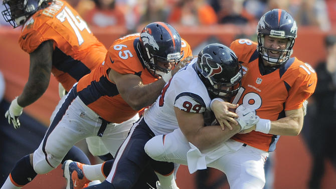 In this Sept. 23, 2012, file photo, Denver Broncos quarterback Peyton Manning (18) is sacked by Houston Texans defensive end J.J. Watt (99) as guard Manny Ramirez (65) tries to block Watt during an NFL football game in Denver. Watt's sacks have gone down from 20 last season to 9 this year, but the Broncos contend this is another case where the numbers don't tell the whole story. The two teams meet again on Sunday, Dec. 22