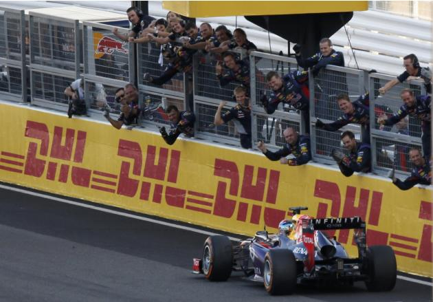 The Red Bull crew congratulates Red Bull Formula One driver Vettel of Germany from the pit wall after he crossed the finish line to win the Japanese F1 Grand Prix at the Suzuka circuit