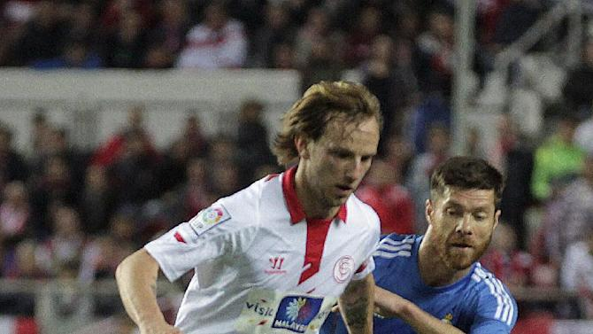 Real Madrid's Xavi Alonso, right, and Sevilla's Ivan Rakitic from Croatia vie for the ball during their La Liga soccer match at the Ramon Sanchez Pizjuan stadium, in Seville, Spain on Wednesday, March 26, 2014