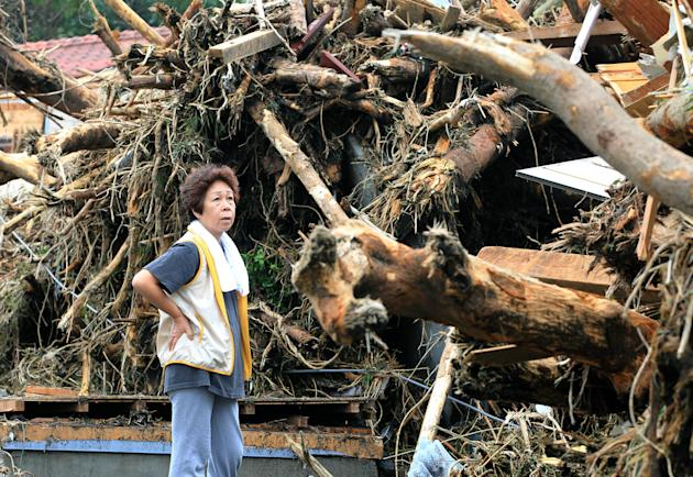 A woman looks at the aftermath of landslides in the rubble of smashed houses in Oshima after a powerful typhoon hit Izu Oshima island, about 120 kilometers (75 miles) south of Tokyo Wednesday morning,