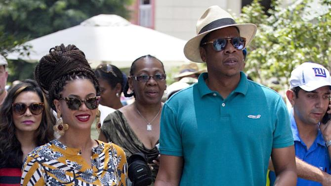 "FILE - This April 4, 2013 file photo shows married musicians Beyonce, left, and rapper Jay-Z as they tour Old Havana, Cuba. Jay-Z is addressing his recent trip to Cuba in a new song. The rapper released ""Open Letter"" Thursday, April 11, after two Florida Republicans questioned if the rapper's visit to Havana with wife Beyonce was officially licensed.  (AP Photo/Ramon Espinosa, file)"