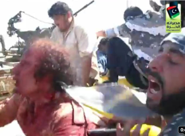 This video frame grab image taken from Libyan TV, purports to show former Libyan leader Moammar Gadhafi alive and surrounded by revolutionary fighters in Libya, Thursday Oct. 20, 2011. Arab satellite