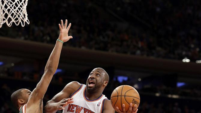 New York Knicks's Raymond Felton, center, shoots against Milwaukee Bucks' Ramon Sessions, left, as Giannis Antetokounmpo watches during the first quarter of an NBA basketball game at New York's Madison Square Garden, Saturday, March 15, 2014