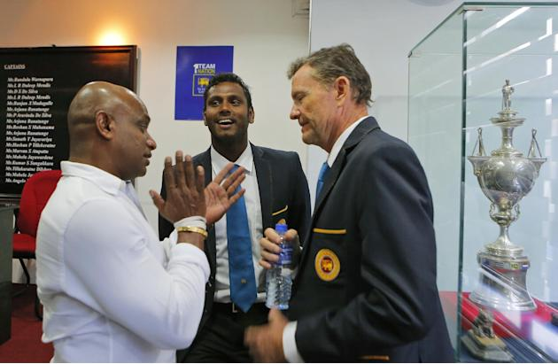 Sri Lankan cricket captain Angelo Mathews, center, coach Graham Ford, right, and chief selector Sanath Jayasuriya chat prior to the team's departure to England at Sri Lankan Cricket office in Colo