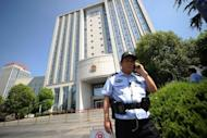 "Security guards stand outside the Intermediate People's Court in Hefei, Anhui province on August 7. The wife of a former Chinese top politician at the heart of a scandal that has rocked the ruling Communist Party has admitted murdering a British businessman and blamed her actions on a ""mental breakdown"", state media reported Friday"