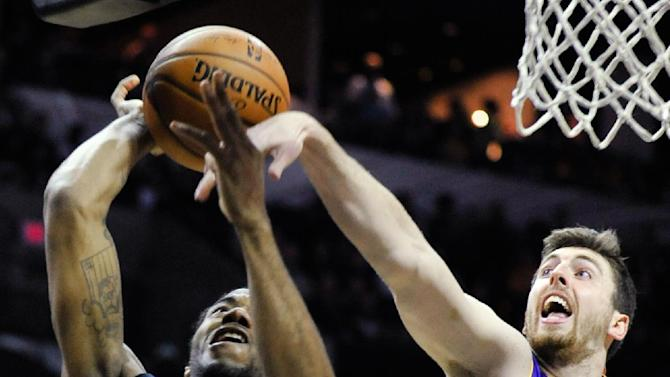 Los Angeles Lakers forward Ryan Kelly, right, defends San Antonio Spurs forward Kawhi Leonard during the first half of an NBA basketball game Friday, March 14, 2014, in San Antonio