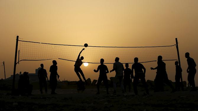 Palestinians play volleyball near the ruins of houses, that witnesses said were destroyed by Israeli shelling during a 50-day war last summer, in Beit Lahiya town in the northern Gaza Strip