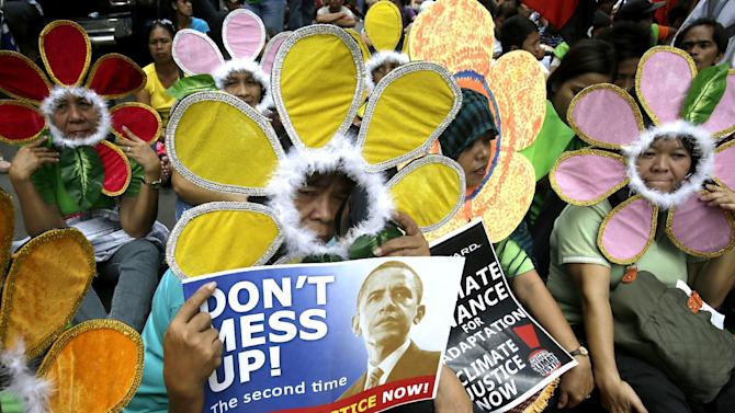 FILE - In this Nov. 14, 2012 file photo, protesters wearing flower costumes, display placards during a rally near the U.S. Embassy in Manila, Philippines to call on industrialized countries to act on the growing problem of climate change. Slowing the buildup of greenhouse gases responsible for warming the planet is one of the biggest challenges the U.S. _ and President Barack Obama _ faces. The impacts of rising global temperatures are widespread and costly: more severe storms, rising seas, species extinctions, and changes in weather patterns that will alter food production and the spread of disease. (AP Photo/Bullit Marquez, File)