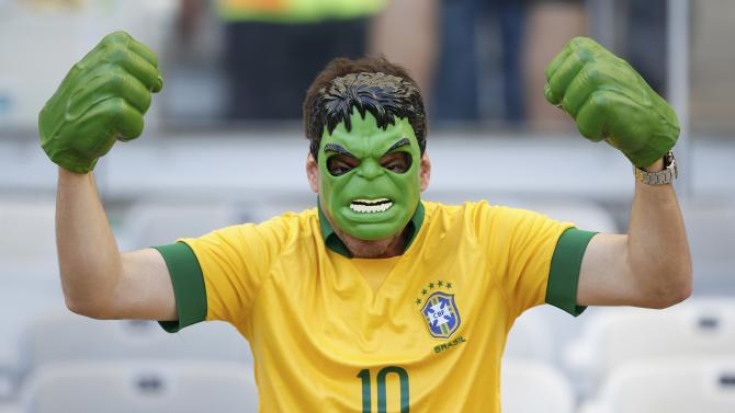 A fan of Brazil gestures as he wears a Hulk costume while waiting for the start of their 2014 World Cup round of 16 game against Chile at the Mineirao stadium in Belo Horizonte