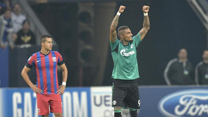 Schalke's Kevin-Prince Boateng, right, celebrates after scoring his team's second goal as Bucharest's Daniel Georgievski, left, stands by, during the Champions League Group E soccer match between FC Schalke 04 and Steaua Bucharest  in Gelsenkirchen, Germany, Wednesday, Sept. 18, 2013