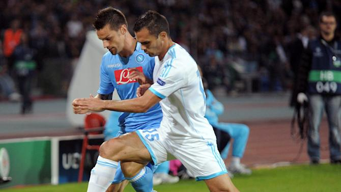 Napoli's Christian Maggio, left, and Marseille's Jeremy Morel vie for the ball during a Champions League, group F, soccer match between Napoli and Marseille, at the Naples San Paolo stadium, Italy, Wednesday, Nov. 6, 2013