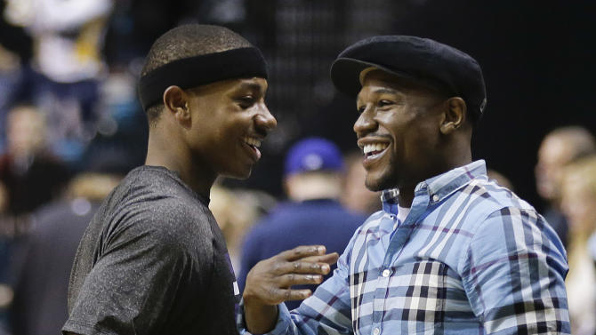 Floyd Mayweather Jr., right, talks with Sacramento Kings point guard Isaiah Thomas (22) after a preseason NBA basketball game against the Los Angeles Lakers, Thursday, Oct. 10, 2013, in Las Vegas.  The Kings won 104-86