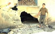 An image grab taken from a video released by the United Nations Supervision Mission in Syria (UNSMIS) shows a youth pointing out a shelled house to UN observer in the central flashpoint city of Homs.