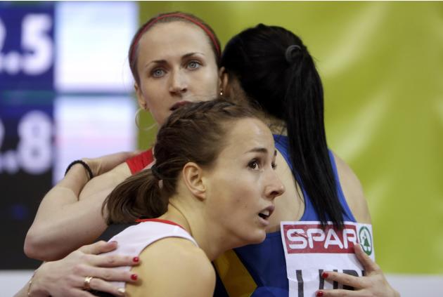 Winner Buchel of Switzerland, second placed Poistogova of Russia and third placed Lupu of Ukraine hug as they wait for official results after their women's 800 metres final during the European Ind
