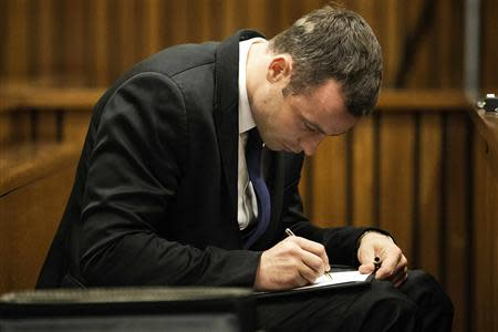 Olympic and Paralympic track star Oscar Pistorius takes notes during the fourth day of his trial for the murder of his girlfriend Reeva Steenkamp at the North Gauteng High Court in Pretoria