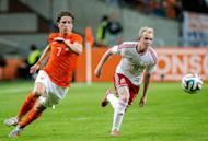 Netherland's Daryl Janmaat (L) and Wales' Jonathan Williams run for the ball during the friendly football match between the Netherlands and Wales on June 4, 2014 in Amsterdam