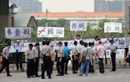 """Anti-China activists display placards reading, """"refuse unificiation with China"""" outside the venue of the eighth Taiwan and China trade talks in Taipei. Some Taiwanese fear a new trade pact with China will strengthen Beijing's hold over the island, and protesters have been tailing China's chief negotiator Chen Yunlin since his arrival on Wednesday"""