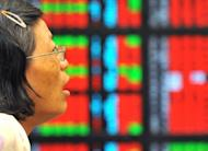 A woman looks at an electronic stock display board at a securities trading house in Taipei in 2011. Taiwan on Wednesday decided to levy capital gains tax on share trading, more than two decades after a previous attempt to do so sparked a plunge in the stock market and was eventually abandoned