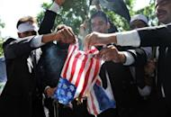 """Pakistani lawyers burn a US flag as they attempt to reach the US embassy in the diplomatic enclave during a protest against an anti-Islam movie in Islamabad on September 19. More than 30 people worldwide have died in incidents linked to the trailer for """"Innocence of Muslims,"""" a US-made film that depicts the Prophet Mohammed as a thuggish womaniser."""