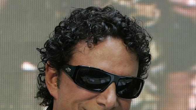 "FILE - In this March 2, 2009 file photo, Neal Schon poses for a photograph during a news conference at a mall in suburban Quezon City, north of Manila, Philippines.  Schon, the lead guitarist for the rock band Journey has filed a federal lawsuit in Minneapolis that accuses his former mother-in-law of libeling him in her blog posts. Schon says Judy Kozan, the former mayor of Waseca, has ""attacked and harassed"" him for years through Internet postings and comments in the media. Schon's lawsuit says Kozan suggested that he has failed to support his ex-wife and their two daughters. (AP Photo/Aaron Favila)"