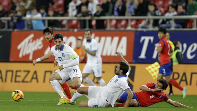 Greece's Alexandros Tziolis, center, and Kostas Katsouranis, second left, fight for the ball with South Korea's Koo Jacheol, right, during a friendly match at Georgios Karaiskakis stadium in Piraeus port, near Athens, Wednesday, March 5, 2014