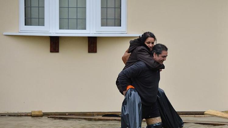 Residents wearing homemade waders evacuate their home in Wraybury, Berkshire, west of London on February 10, 2014