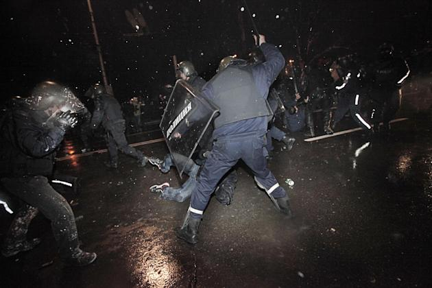 Protesters are beaten and detained by riot police during a protest against high electricity prices in Sofia, on late Tuesday, Feb. 19, 2013.  Bulgaria's prime minister announced on Tuesday that the li