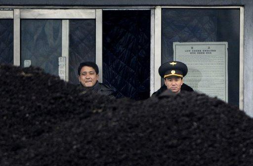A photo taken from Dandong, China, on on December 14, 2012, shows a North Korean military officer (R) peering across the border. N.Korea confirmed Friday that it had arrested a US citizen in November, saying he had admitted to unspecified charges and suggesting he would be formally prosecuted.
