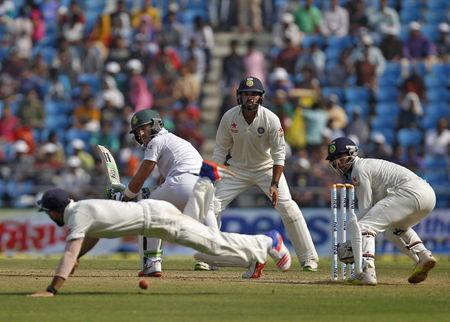 South Africa's Plessis plays a shot as India's captain Kohli dives to catch the ball as IndiaÕs Vijay and wicketkeeper Saha watch during the third day of their third test cricket match in Nagp