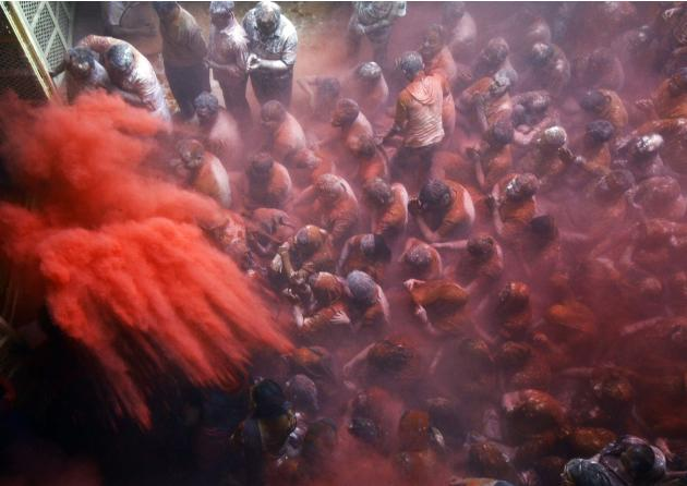 A Hindu priest throws coloured powder on devotees during Holi celebrations in Kolkata