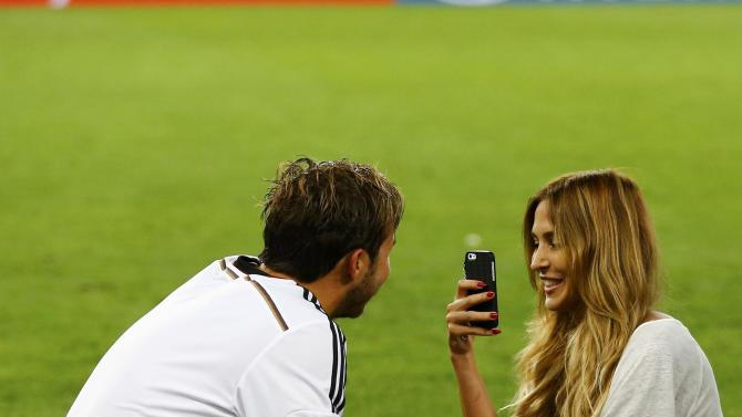 Germany's Goetze has his picture taken by model girlfriend Ann-Kathrin Brommel after they won their 2014 World Cup final against Argentina at the Maracana stadium in Rio de Janeiro