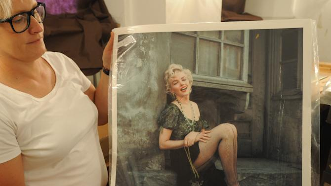 FILE - In this July 20, 2012 file photo gallery curator Anna Wolska presents a photo of Marylin Monroe by the late celebrity photographer Milton H. Greene,  in Warsaw, Poland.  Some 238 pictures by the late photographer Milton H. Greene including portraits of Monroe, along with Cary Grant, Frank Sinatra, Audrey Hepburn, Liza Minnelli, Marlene Dietrich, Paul Newman, Alfred Hitchcock and Marlon Brando, which are to be auctioned off in Warsaw on Thursday Nov. 8, 2012.  Proceeds from the auction will go to the Polish state which owns a collection of around 4,000 pictures by Greene. (AP Photo/Alik Keplicz, File)
