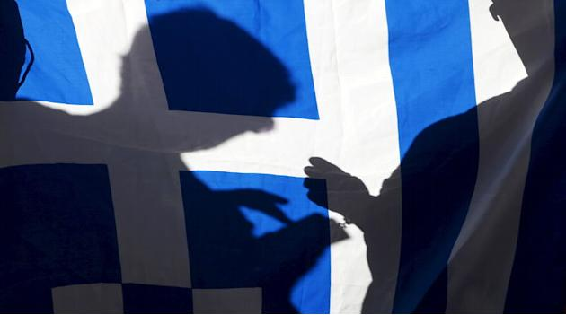 The silhouette of a man using a mobile phone is seen on a Greece flag during a pro-Greece protest in Barcelona