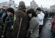 People gather during a rally in the Independence Square in Kiev, Monday, April 14, 2014. Ukraine's acting president urged the United Nations on Monday to send peacekeeping troops to eastern Ukraine, where pro-Russian gunmen kept up their rampage of storming and occupying local government offices, police stations and a small airport. (AP Photo/Sergei Chuzavkov)