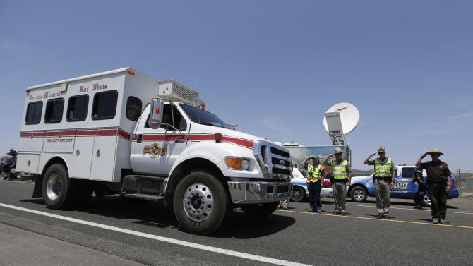 Officials salute and offer a moment of silence as a procession of the vehicles left by the 19 elite Hotshot crew members killed over the weekend are removed from the fire area near Yarnell, Ariz., Wednesday, July 3, 2013. Violent wind gusts on Sunday turned a small, lightning-ignited forest fire in the town into an out-of-control wildfire that left no escape for the team of Hotshots. (AP Photo/Chris Carlson)